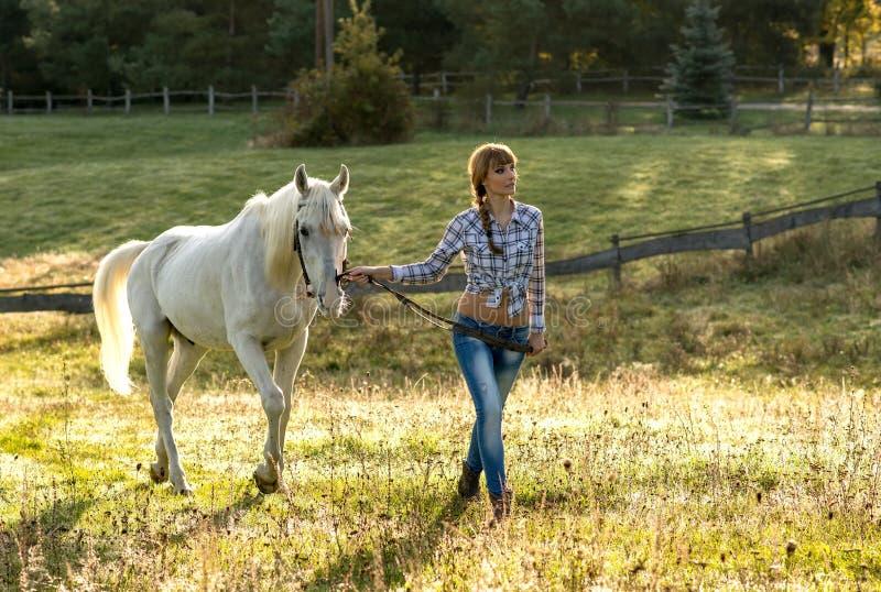 Красивая молодая женщина с белой лошадью в стране стоковые изображения