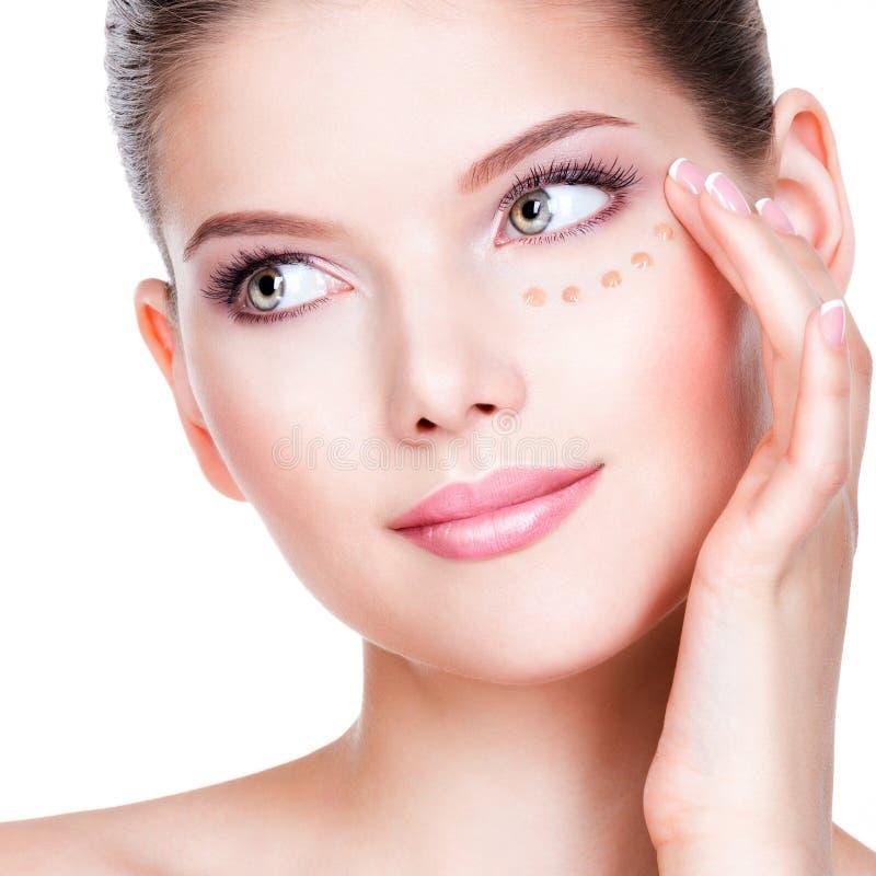 Красивая молодая женщина с косметическим учреждением на коже стоковое изображение