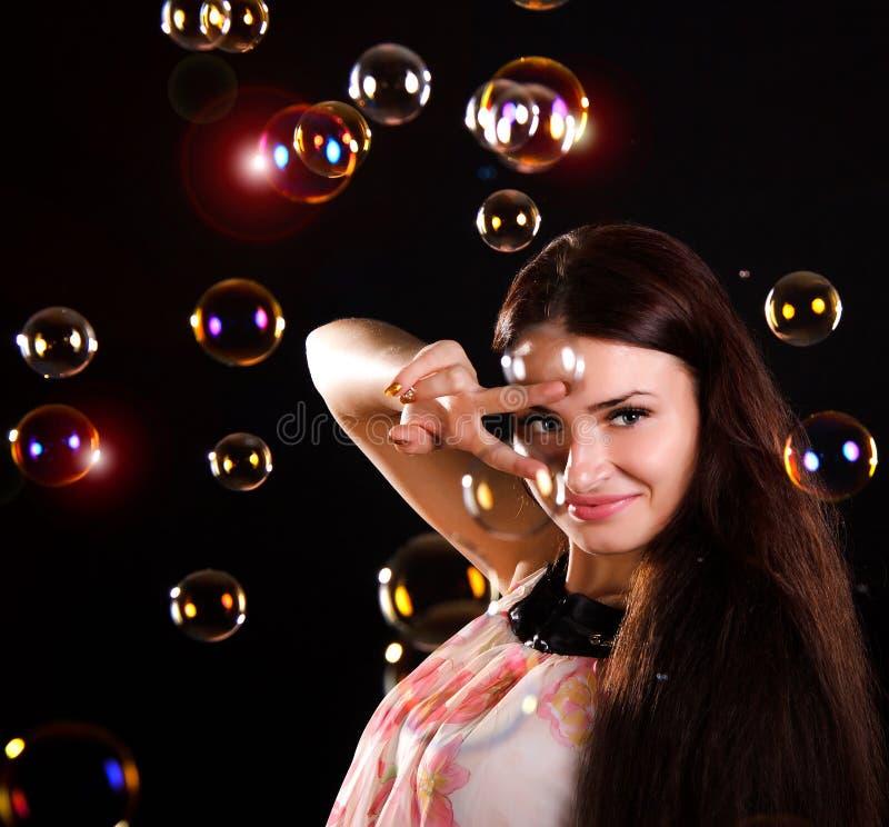 Красивая молодая женщина с пузырями мыла стоковое фото rf