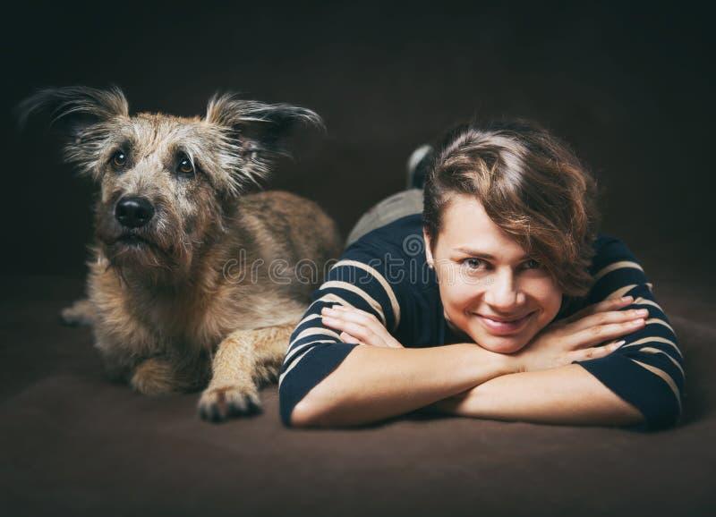 Красивая молодая женщина с смешной shaggy собакой на темном backgrou стоковая фотография