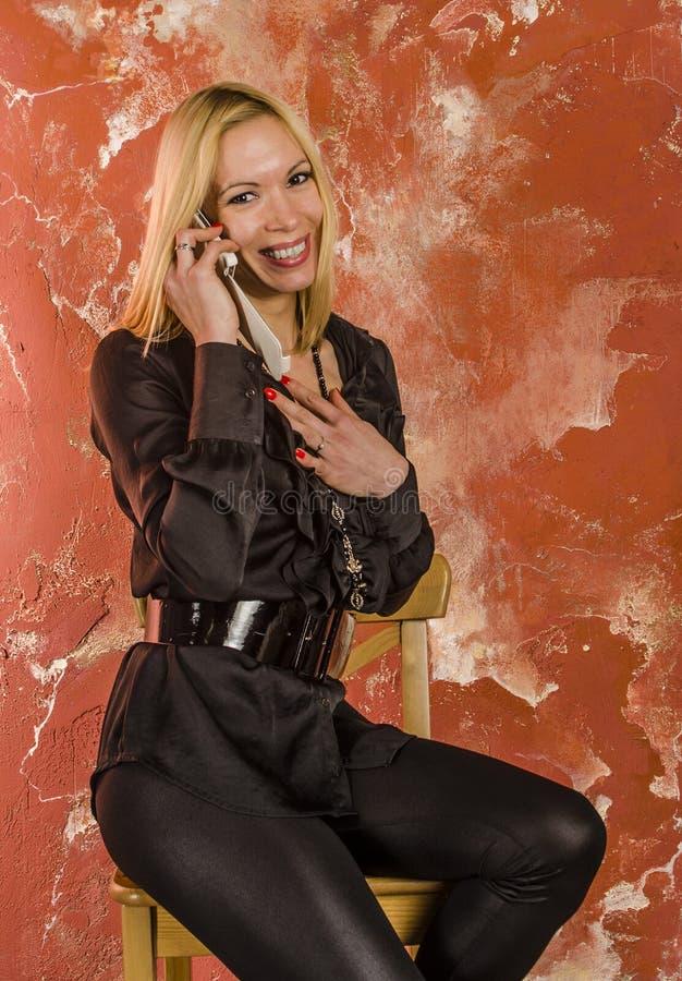 Красивая молодая женщина с сумкой моды и в черной рубашке эмоционально говоря на телефоне стоковая фотография