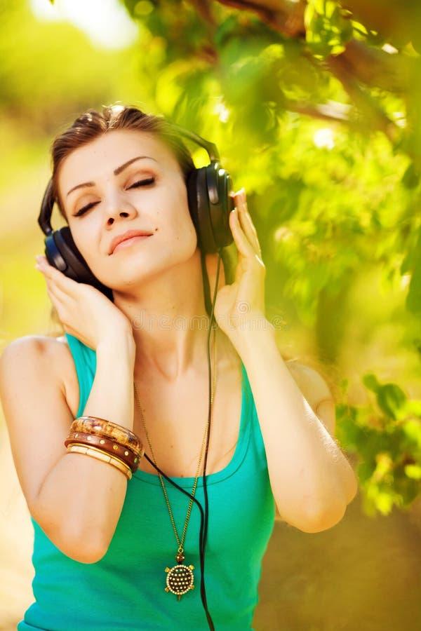 Красивая молодая женщина слушает к наушникам музыки нося внешним стоковая фотография