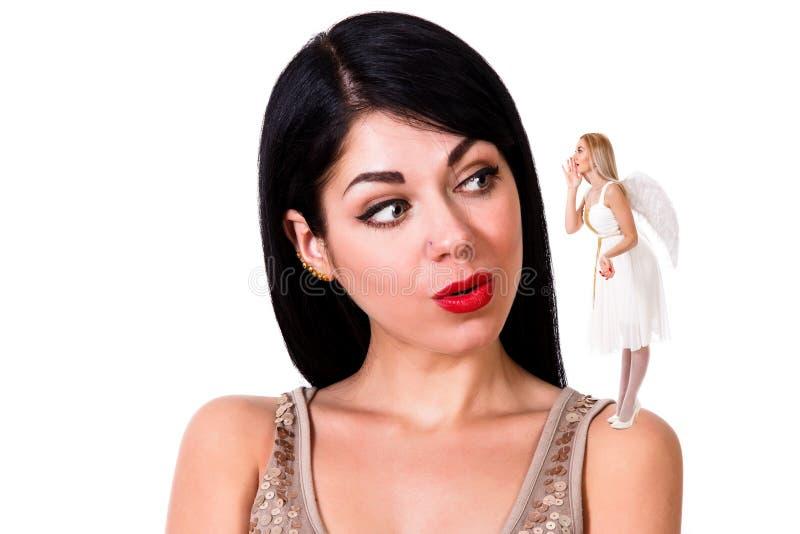 Красивая молодая женщина слушая к ангелу оставаясь на ее shou стоковые фотографии rf
