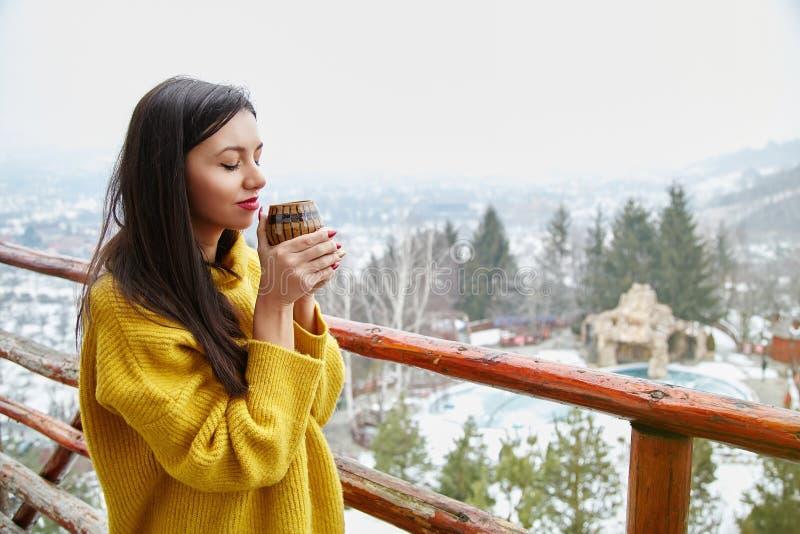 Красивая молодая женщина с чашкой кофе на предпосылке зимы стоковая фотография rf