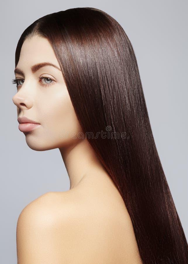 Красивая молодая женщина с чистой кожей, красивыми прямыми сияющими волосами, составом моды стоковые изображения rf