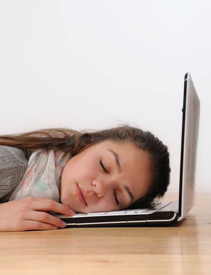 Красивая молодая женщина уснувшая на ее компьтер-книжке против белого backg стоковая фотография rf