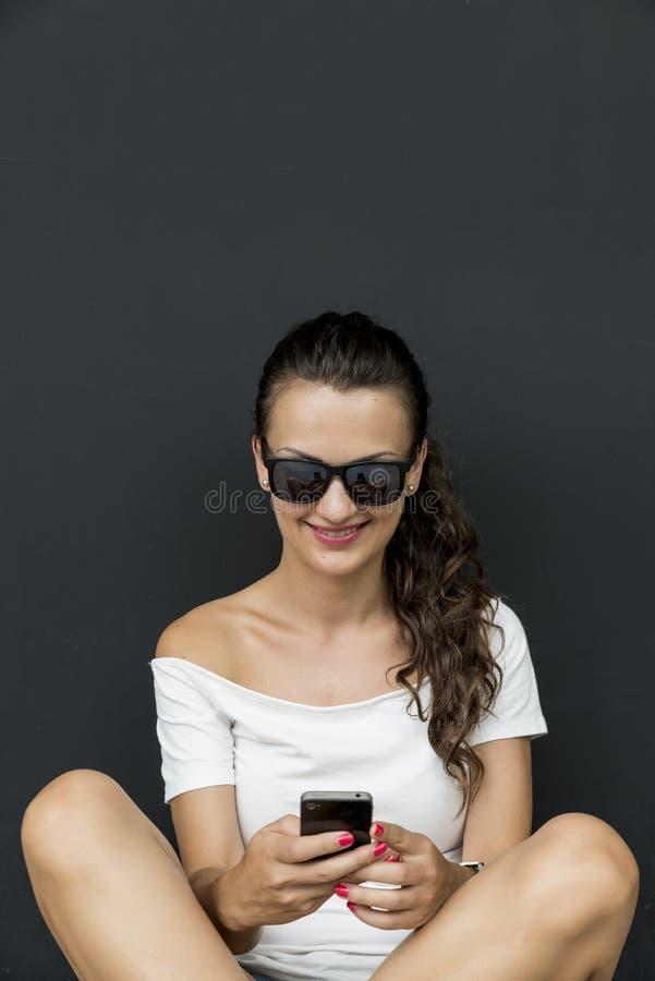 Красивая молодая кавказская женщина при smartphone, отправляя СМС стоковое изображение rf