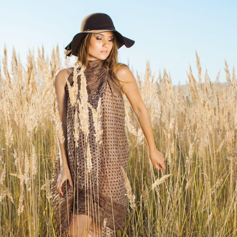 Красивая молодая модель идя через tallgrass - outdoors снял стоковые изображения