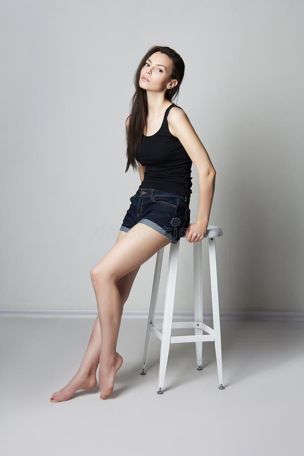 Красивая молодая модель сидя на барном стуле стоковая фотография rf