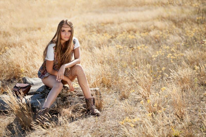 Красивая молодая модель сидя на пне в поле на восходе солнца стоковые фотографии rf