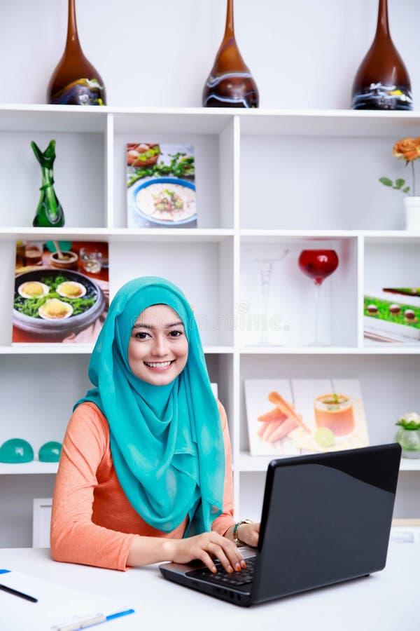 Красивая молодая мусульманская женщина работая на ее компьтер-книжке стоковое фото