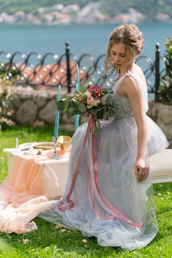 Красивая молодая невеста на лужайке представляет для фото стоковое изображение rf