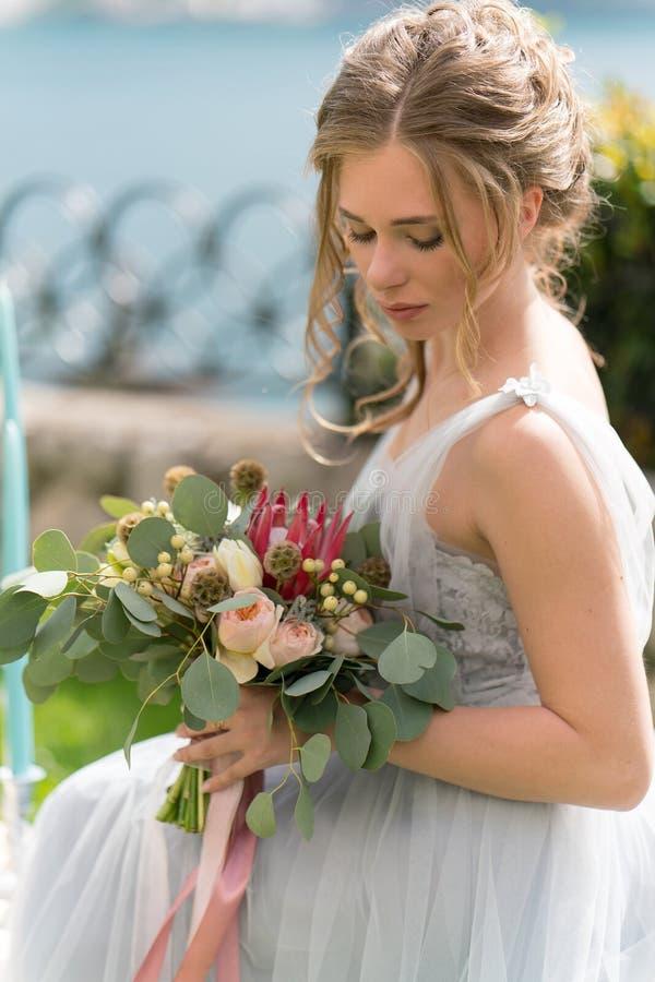 Красивая молодая невеста на лужайке представляет для фото стоковое изображение