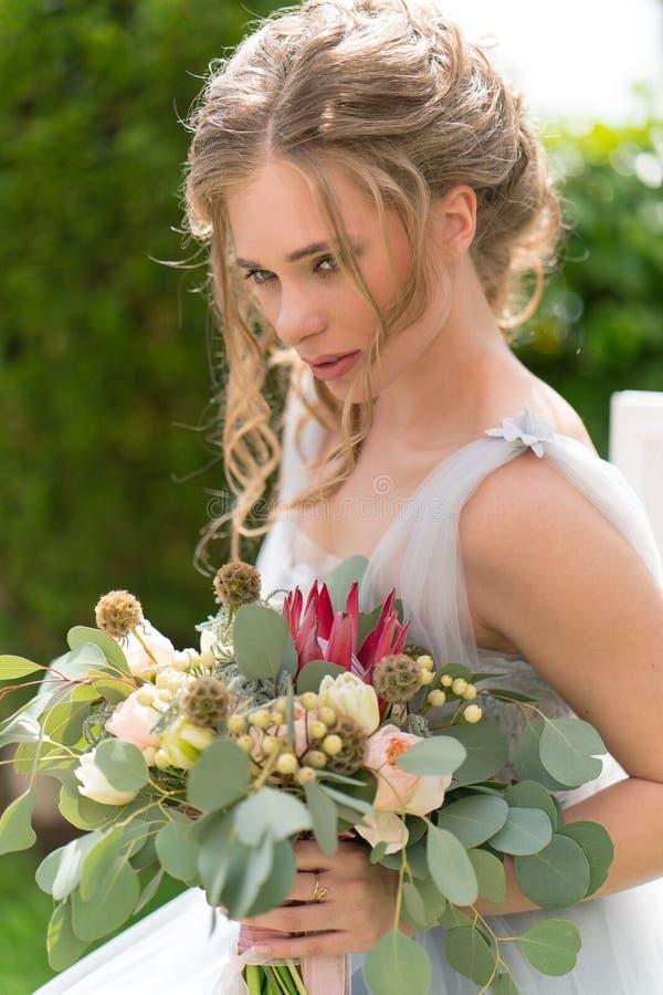 Красивая молодая невеста на лужайке представляет для фото стоковое фото rf