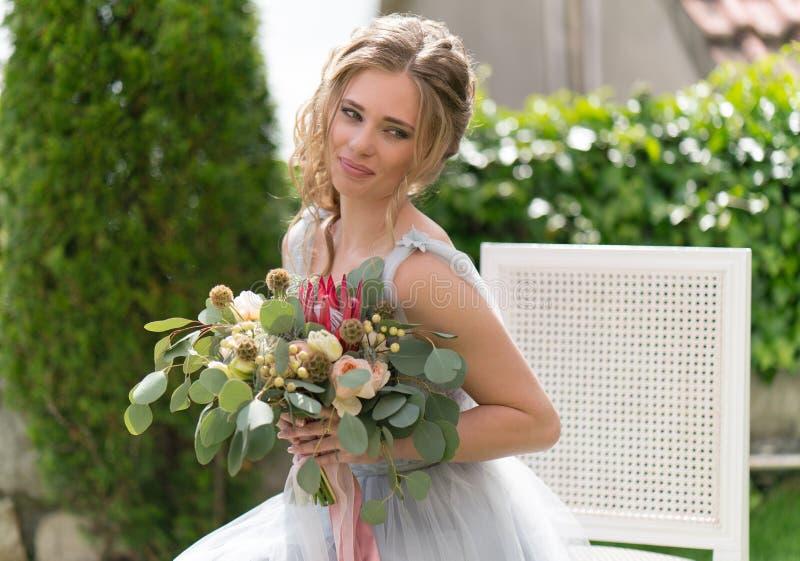 Красивая молодая невеста на лужайке представляет для фото стоковые изображения rf