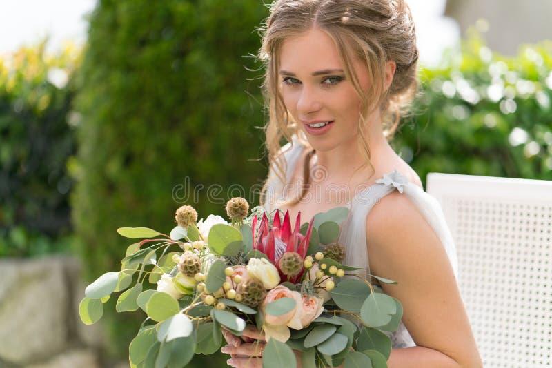Красивая молодая невеста на лужайке представляет для фото стоковое фото