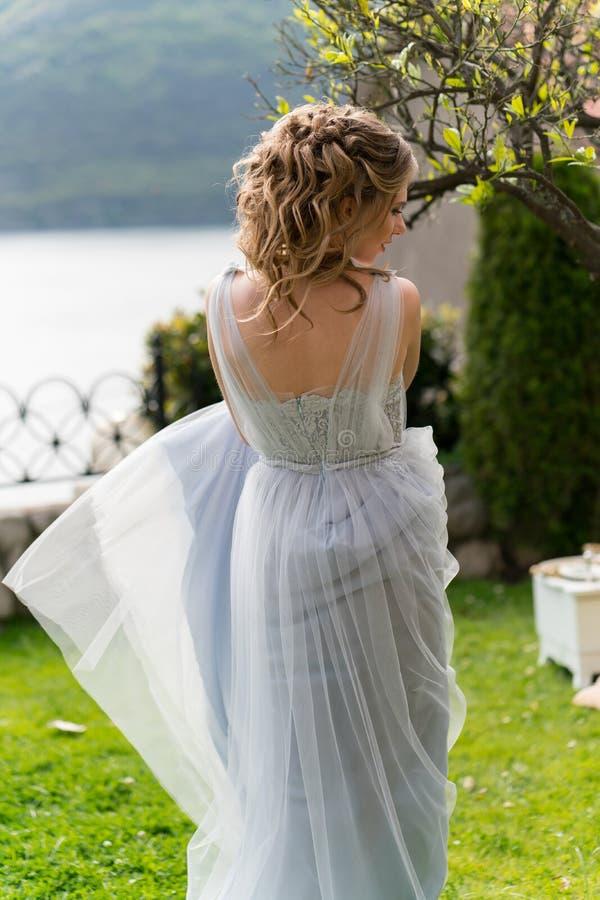 Красивая молодая невеста на лужайке представляет для фото стоковая фотография
