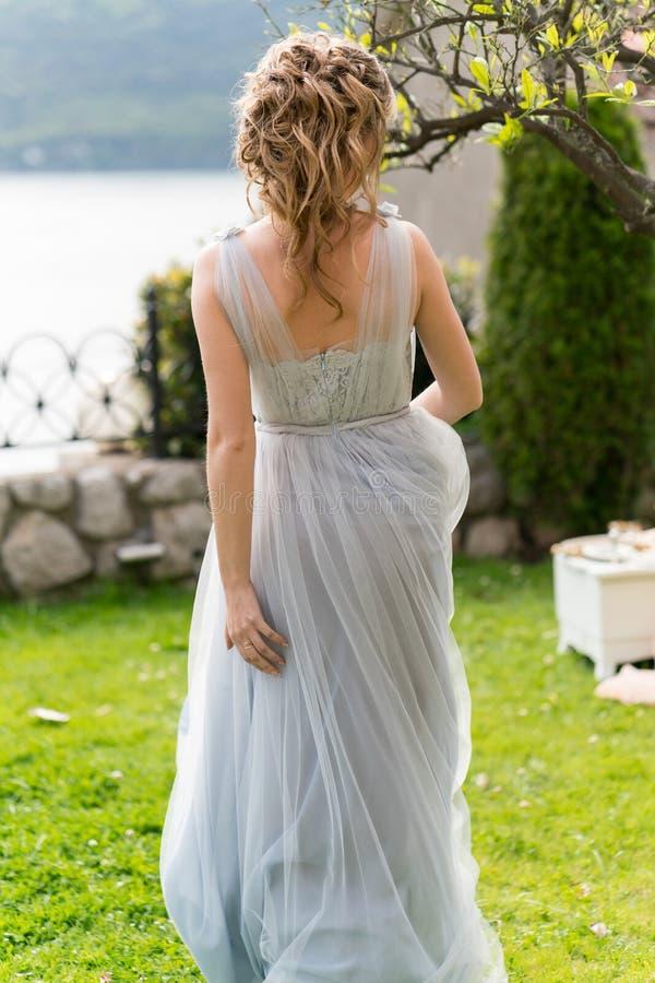 Красивая молодая невеста на лужайке представляет для фото стоковые фото