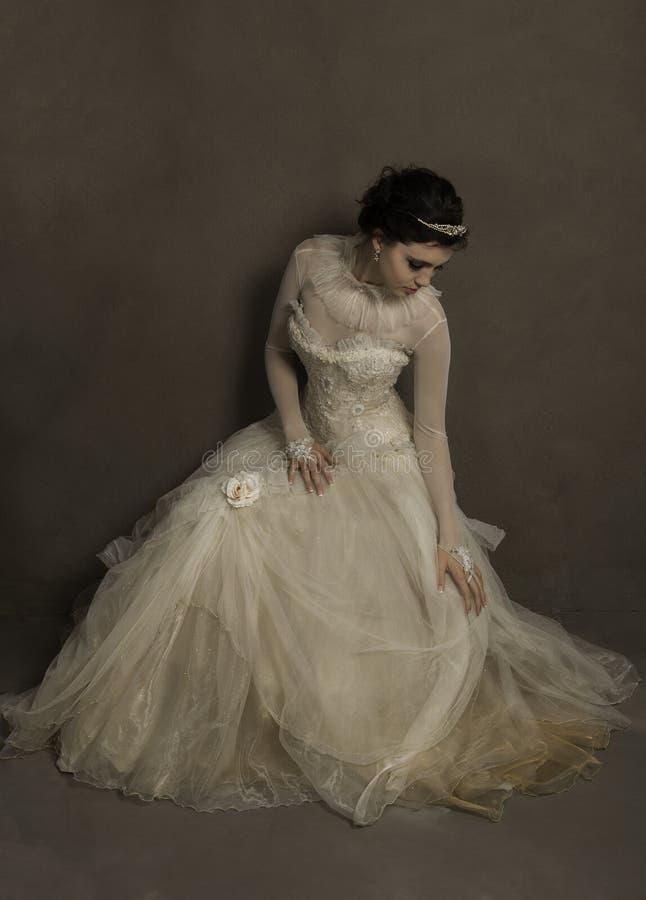 Красивая молодая невеста устанавливая ее винтажное платье свадьбы стоковая фотография