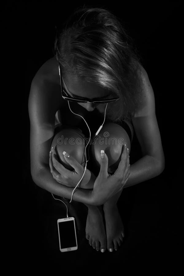 Красивая молодая обнажённая женщина сидя и слушая к музыке в белом smartphone в наушниках и солнечных очках стоковые изображения rf