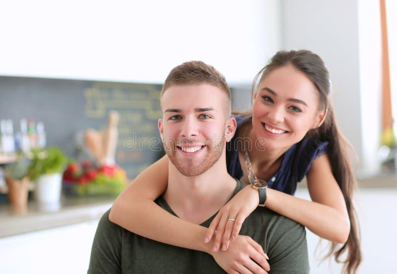 Красивая молодая пара имеет потеху в кухне дома стоковая фотография rf
