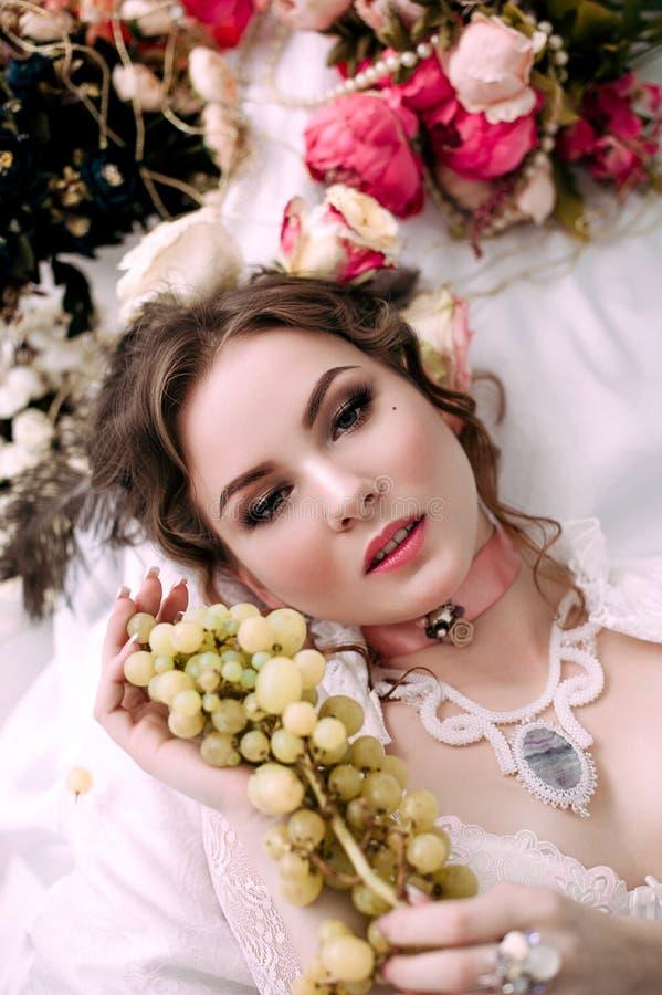 Красивая молодая сексуальная женщина сидя на белой кровати и есть виноградины, нося белое платье шнурка, комнату украшенную с цве стоковые изображения rf
