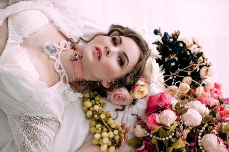 Красивая молодая сексуальная женщина сидя на белой кровати и есть виноградины, нося белое платье шнурка, комнату украшенную с цве стоковое изображение rf