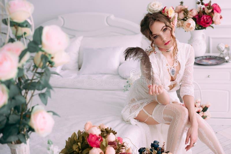 Красивая молодая сексуальная женщина сидя на белой кровати, нося белом платье шнурка, волосах украшенных с цветками Совершенный с стоковое фото rf