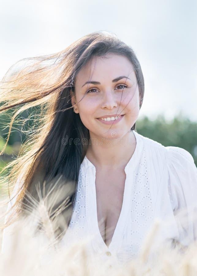 Красивая молодая сексуальная женщина с порхая длинными волосами в ветре Портрет милой усмехаясь девушки на природе стоковые фото