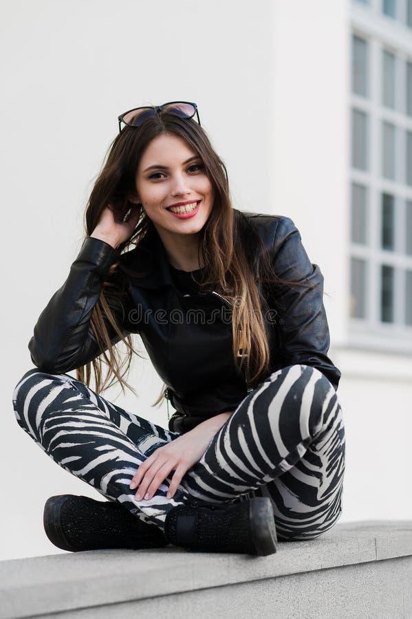Красивая молодая студентка в куртке сидя вниз на старой каменной стене outdoors и усмехаясь во время весеннего дня осени стоковое фото rf