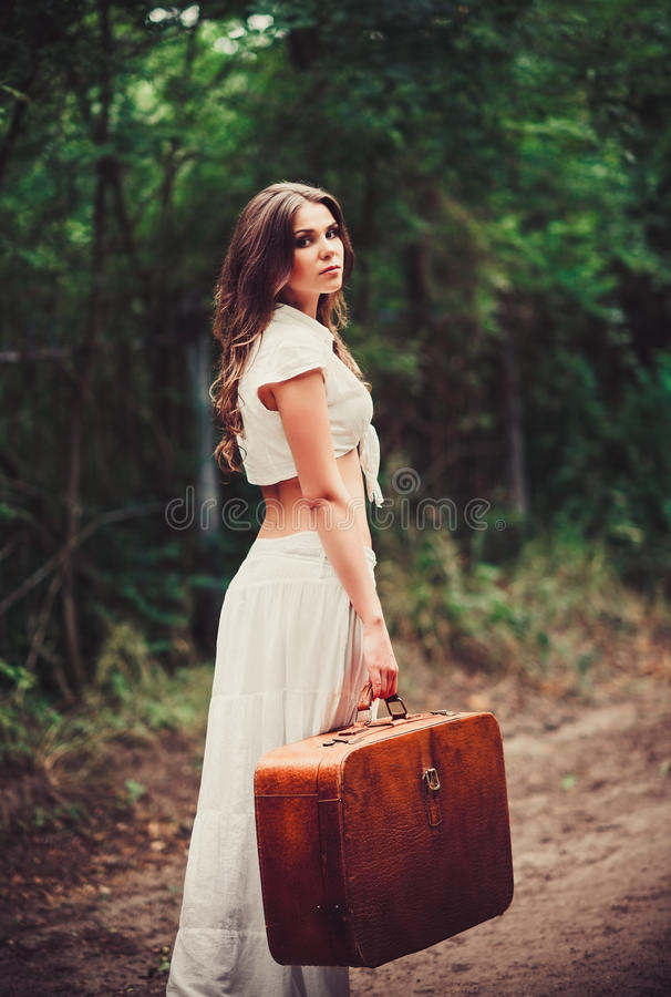 Красивая молодая унылая женщина с чемоданом в руке стоя на дороге стоковое изображение