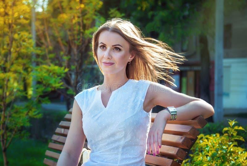 Красивая молодая усмехаясь женщина, сидя на стенде в парке стоковые изображения