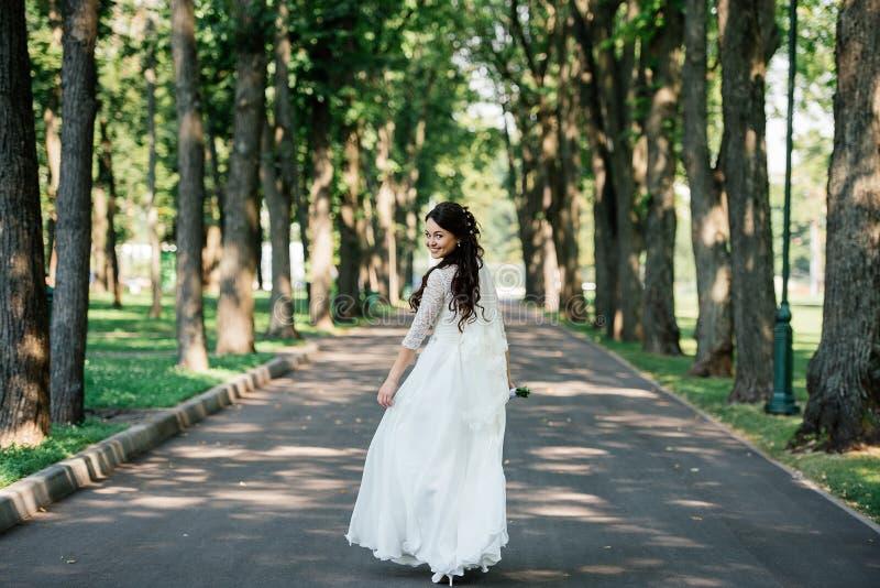 Красивая молодая усмехаясь невеста брюнет в платье свадьбы с букетом цветков в руках outdoors на предпосылке зеленых листьев стоковые фотографии rf