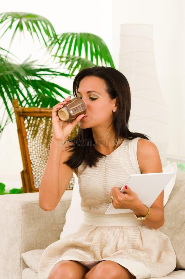 Красивая молодая элегантная женщина сидя в софе стоковое фото rf