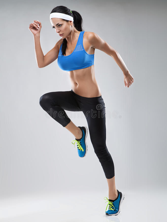 Красивая молодая jogging женщина. Изолированный над белой предпосылкой (c стоковые изображения