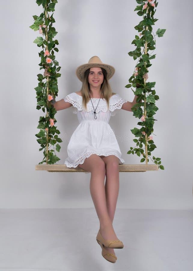 Красивая молодая leggy блондинка в меньших белом платье и белой ковбойской шляпе на качании, деревянном качании приостанавливанно стоковое фото