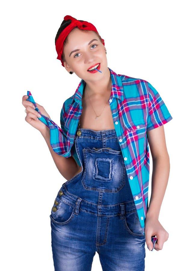 Красивая молодая leggy blondy девушка в красном bandana, прозодеждах джинсовой ткани и рубашке шотландки, лижа конфету Изолирован стоковые изображения