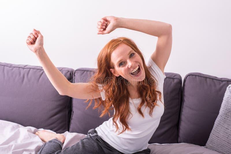 Красивая, молодая, redheaded женщина развевает ее оружия стоковое фото rf