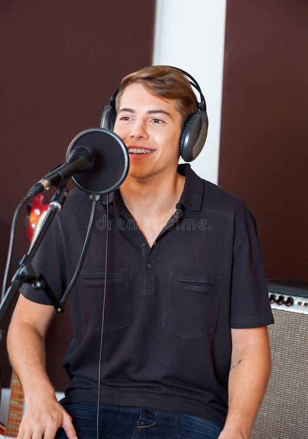 Красивая мужская певица выполняя в студии стоковое изображение rf