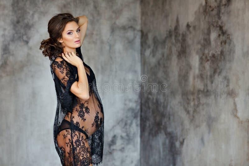 Красивая мягкая и чувственная беременная женщина в черном прозрачном d стоковое фото