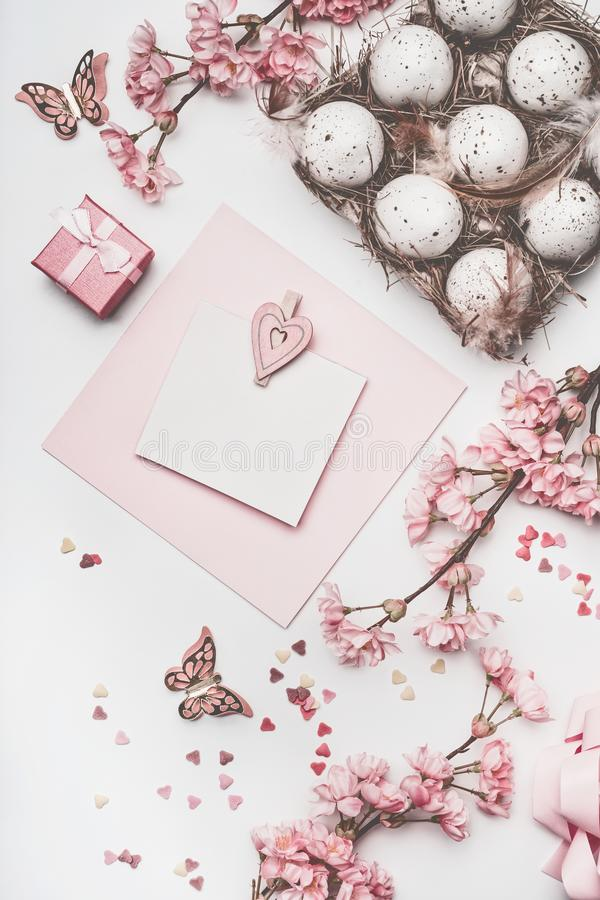 Красивая насмешка поздравительной открытки пасхи пастельного пинка вверх с украшением цветения, сердцами, яичками в коробке короб стоковая фотография
