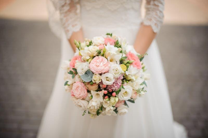 Красивая невеста в белом платье держит букет outdoors стоковые фото