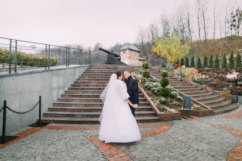 Красивая невеста в длинном белом платье представляя с красивым groom около лестниц outdoors Старый карамболь на предпосылке стоковое фото rf