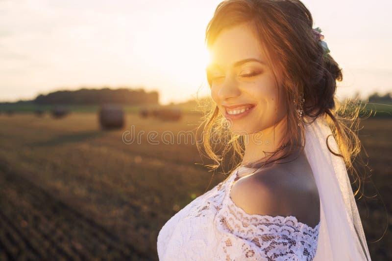 Красивая невеста в платье шнурка усмехается на предпосылке природы стоковое изображение rf