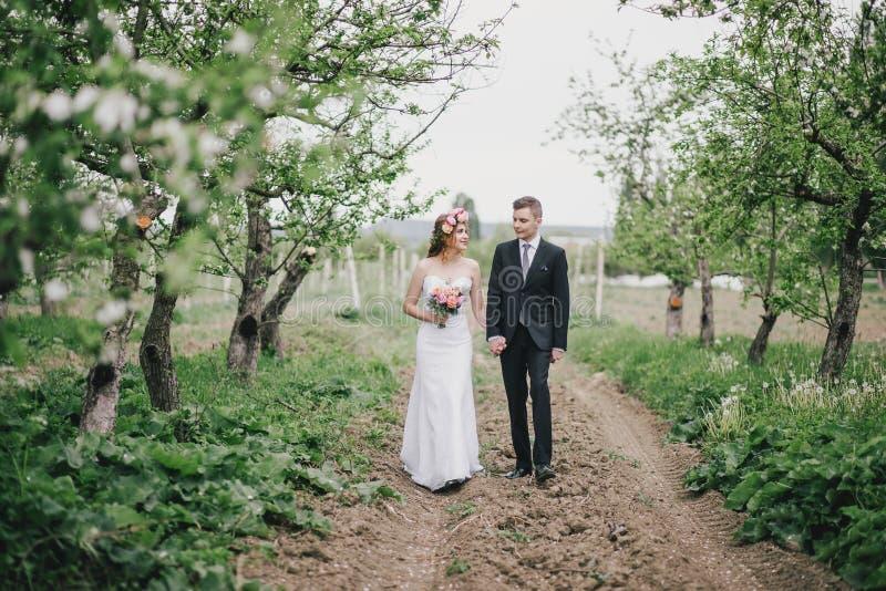 Красивая невеста в платье свадьбы при венок букета и роз представляя с костюмом свадьбы groom нося стоковые изображения