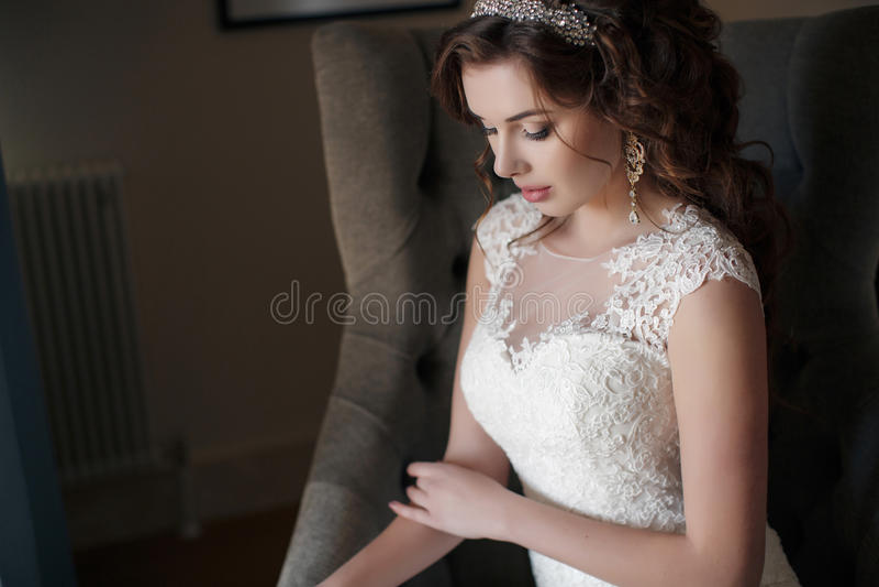 Красивая невеста в платье свадьбы сидя в стуле в гостиничном номере стоковые изображения rf