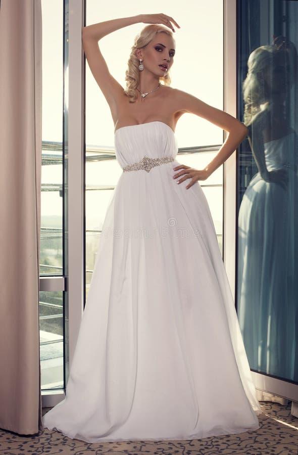 Красивая невеста очарования с светлыми волосами в элегантном платье стоковое изображение
