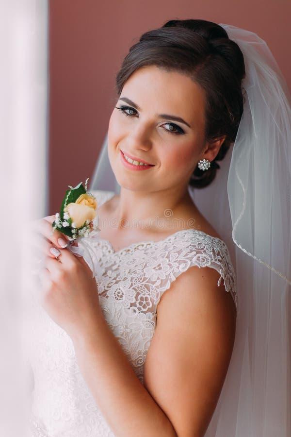 Красивая невеста при очаровательная улыбка представляя около окна держа милое buttonniere стоковая фотография rf