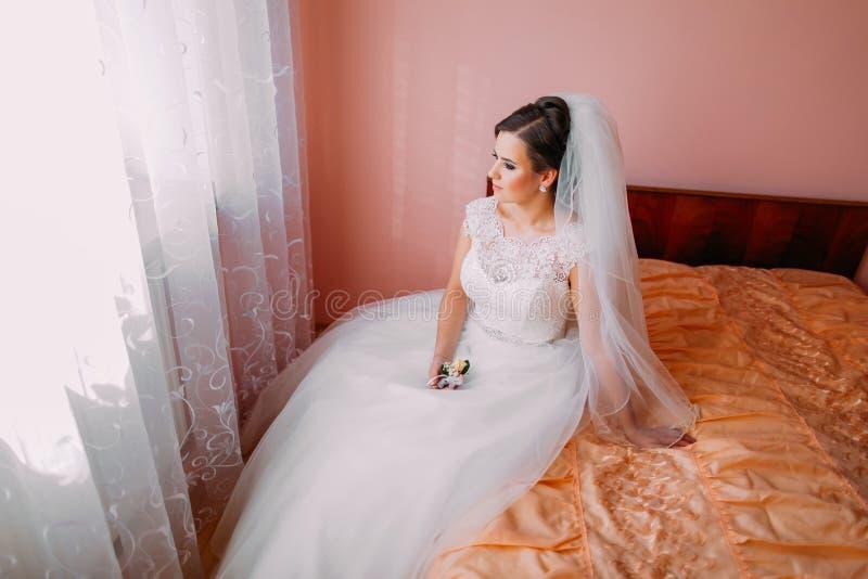 Красивая невеста сидя на кровати в ждать и держать милый маленький boutonniere свадьбы стоковые фотографии rf