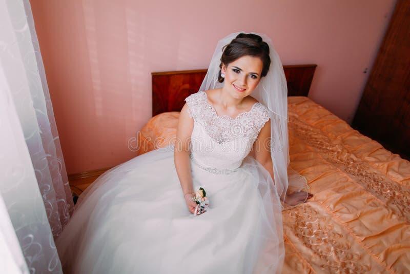 Красивая невеста сидя на кровати около окна в ждать и держать милый маленький boutonniere свадьбы стоковые изображения rf